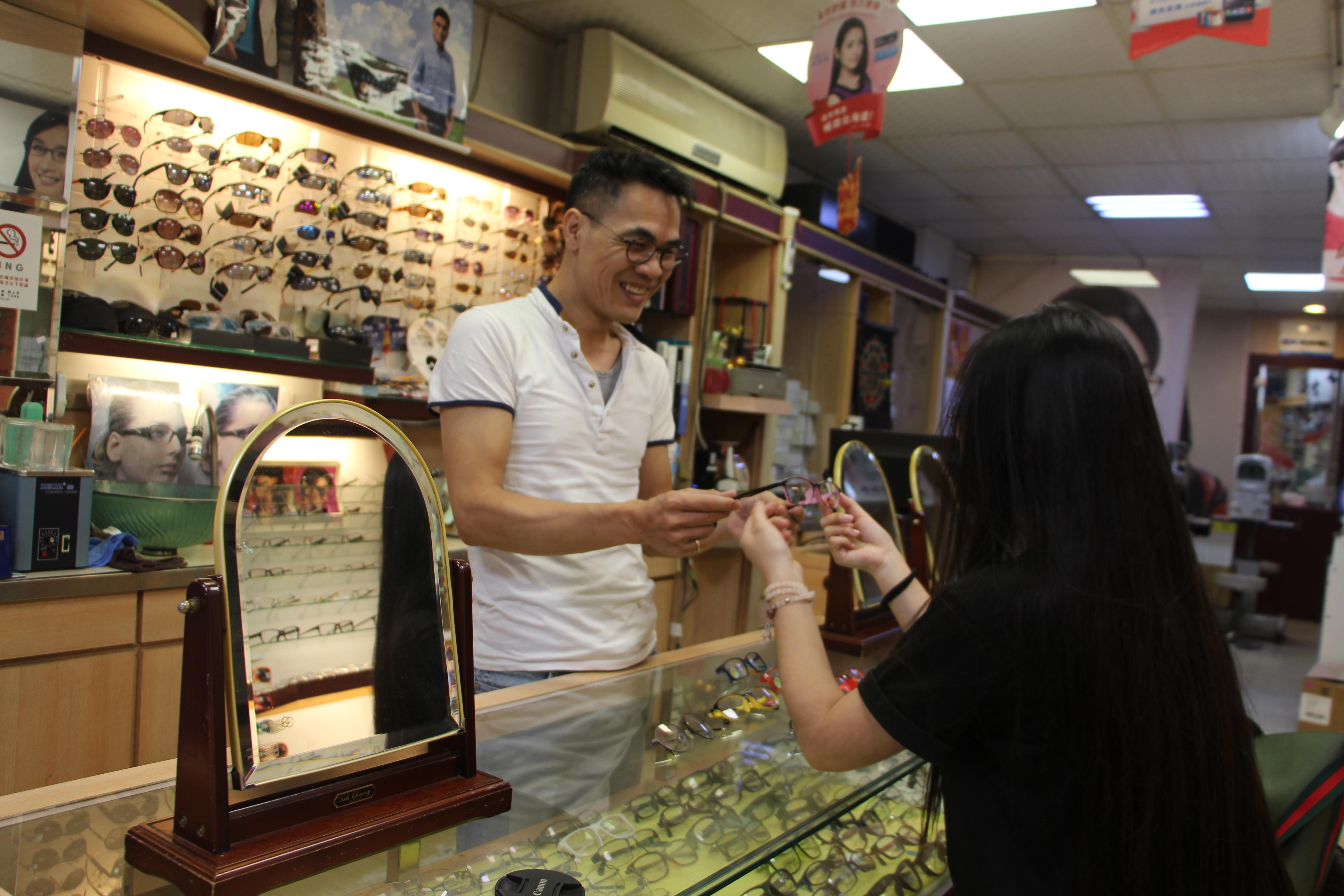 模範眼鏡陳世昌為客人挑選眼鏡。攝影/蘇蓉