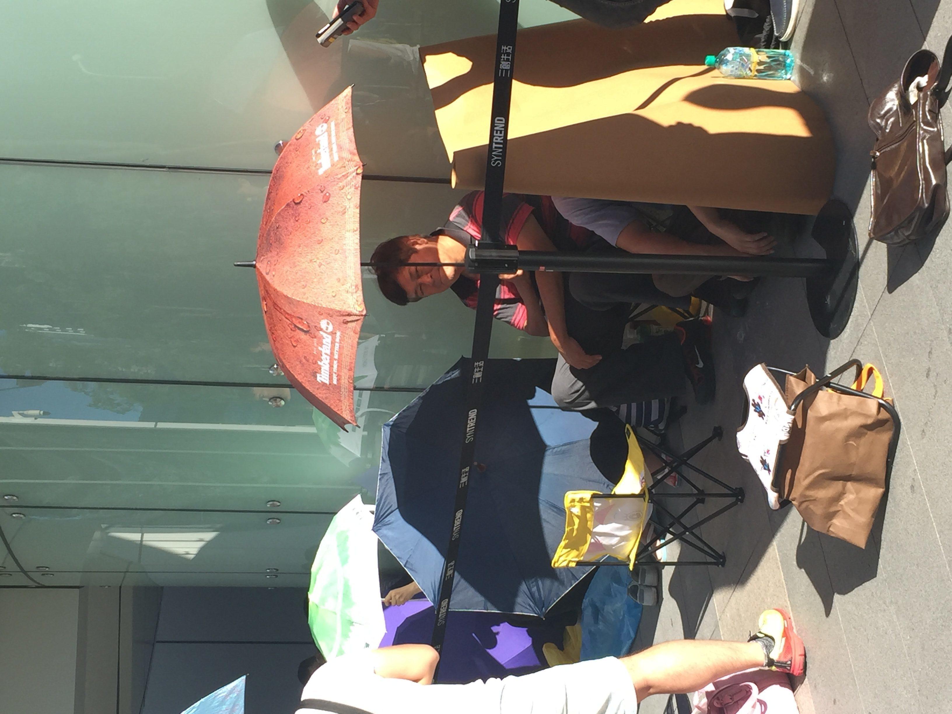 民眾頂著豔陽撐傘排隊購機