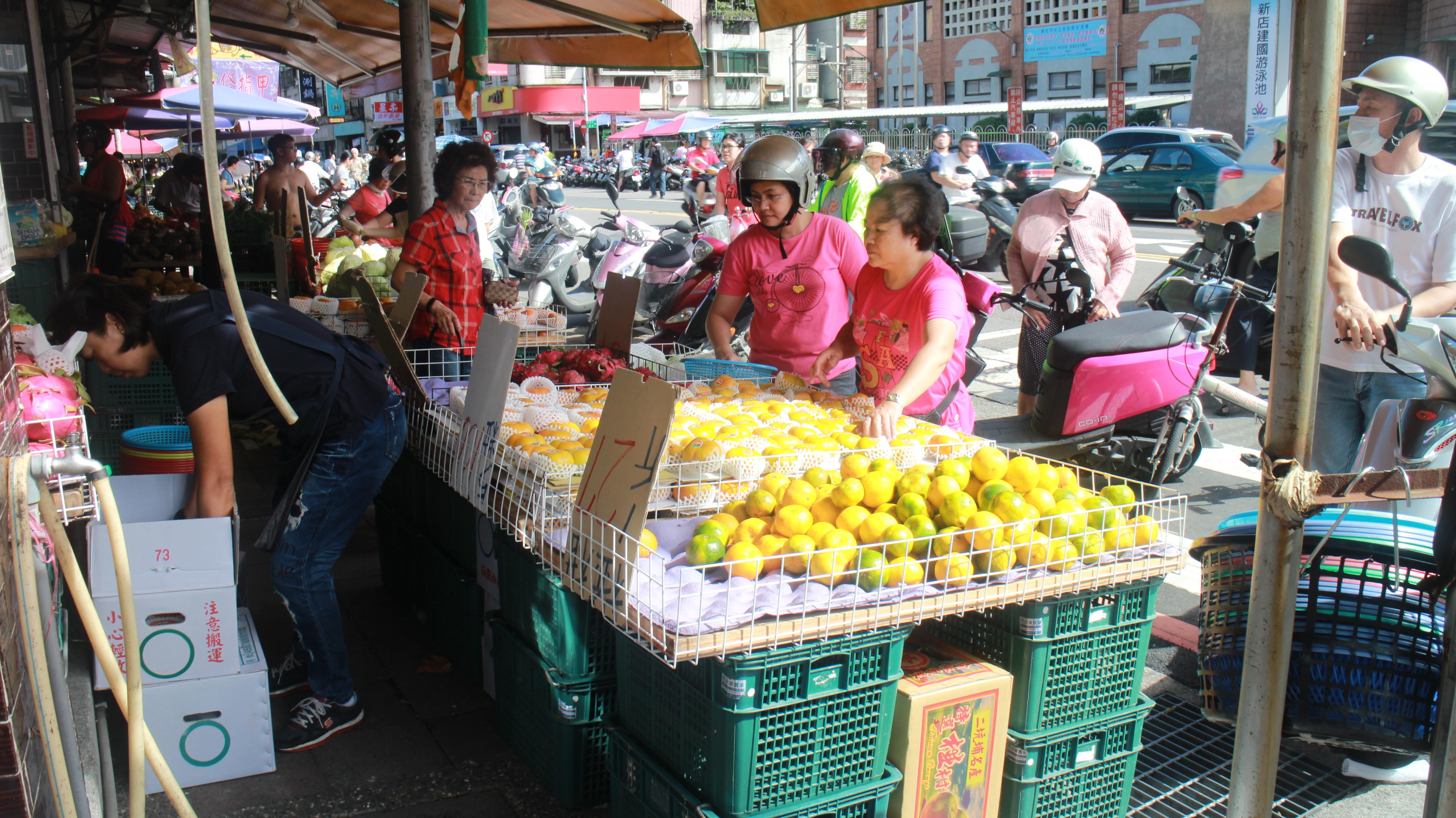 民眾前往攤商採買水果。攝影/林昱萱
