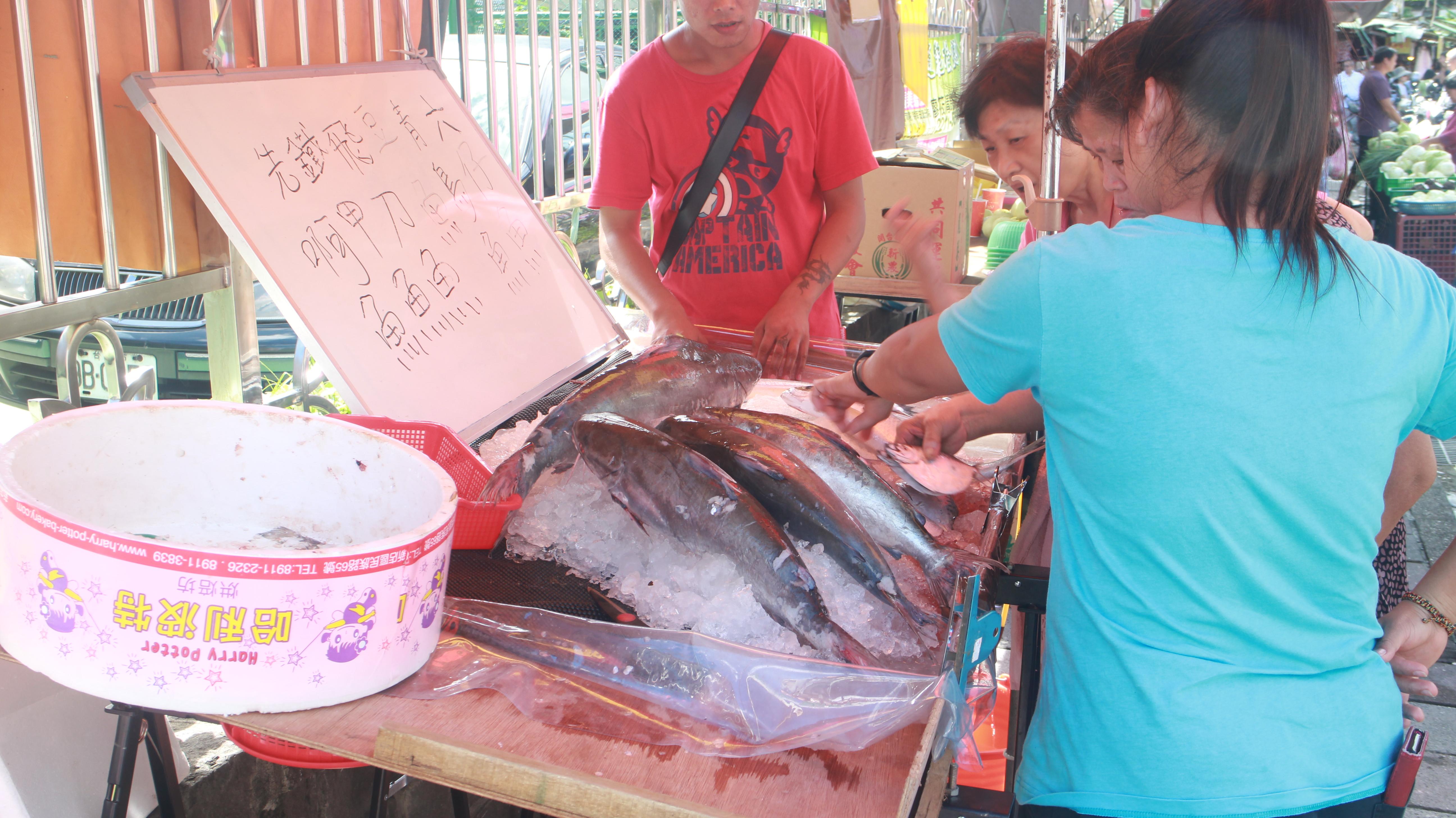 攤商向民眾推銷各式魚類。攝影/林昱萱