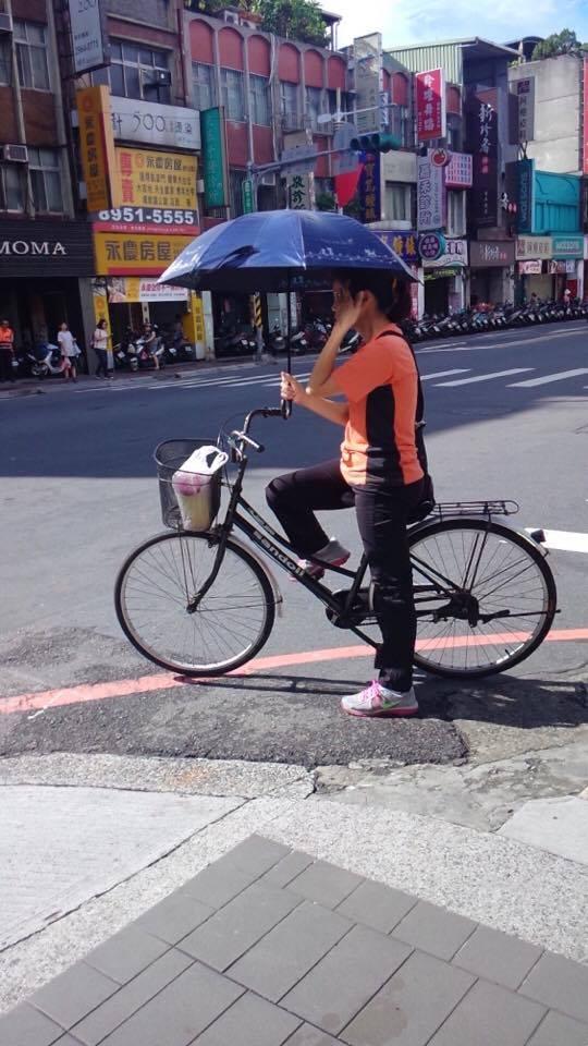 熱辣辣的夏日,民眾連騎腳踏車都不忘撐傘遮陽。(攝影/羅思霓)
