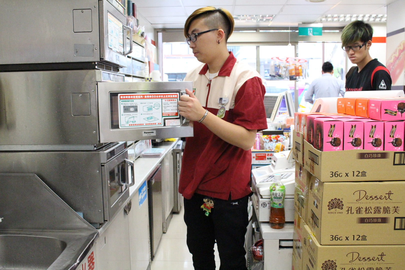 便利商店員工正在幫客人熱便當。攝影/謝孟儒