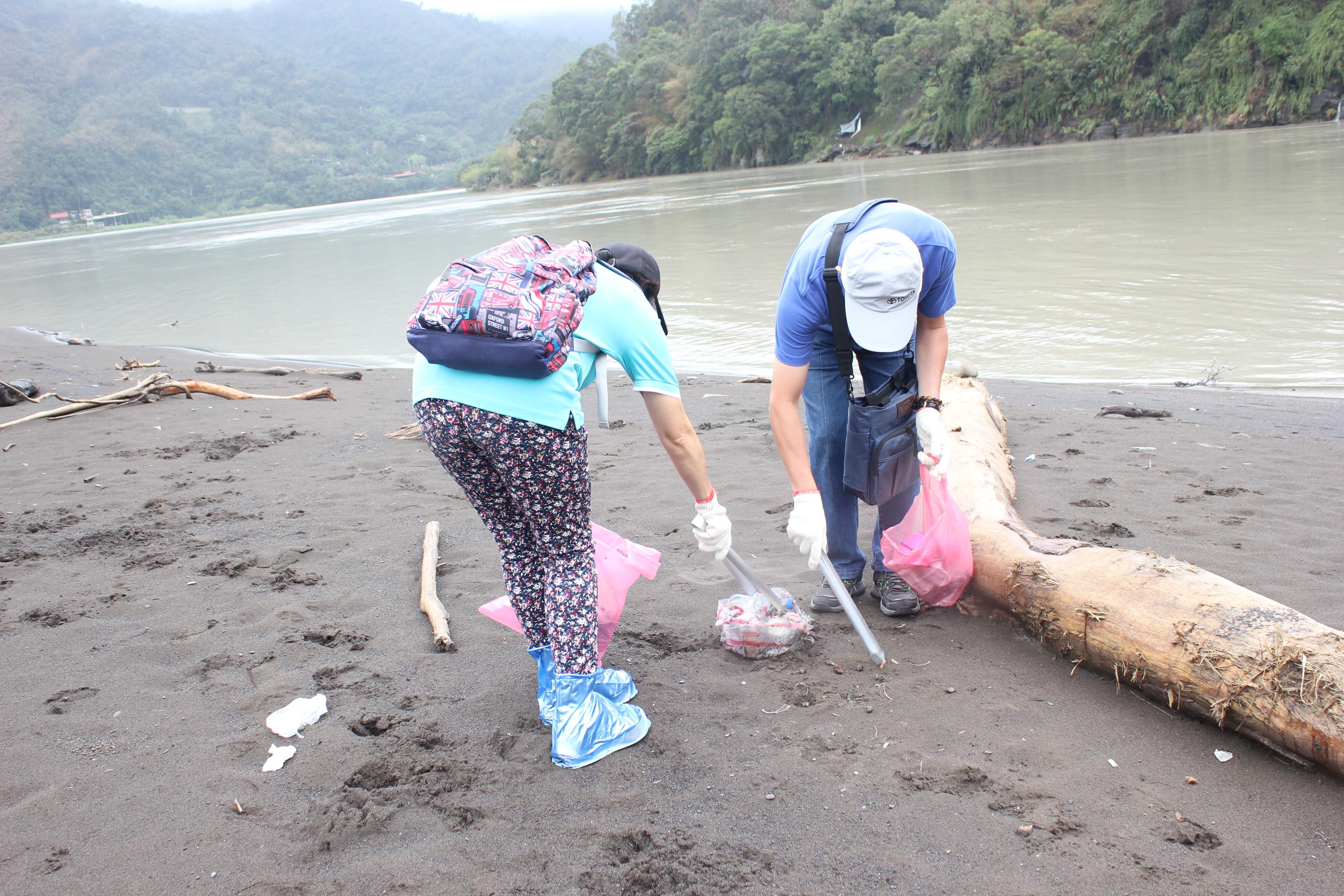 志工將遍布沙灘上的垃圾清除。