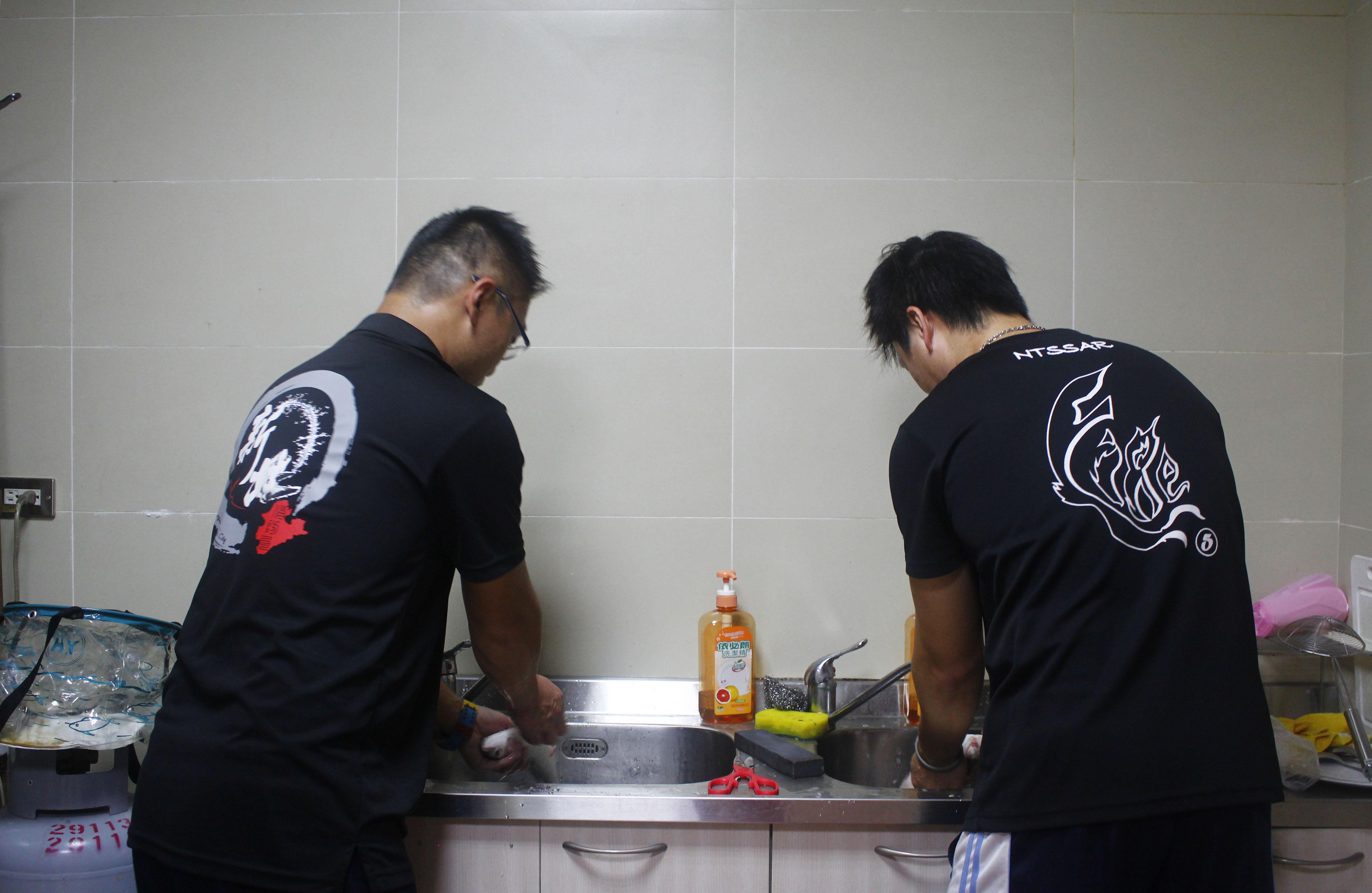 二位消防員在廚房處理魚只。攝影/韋可琦
