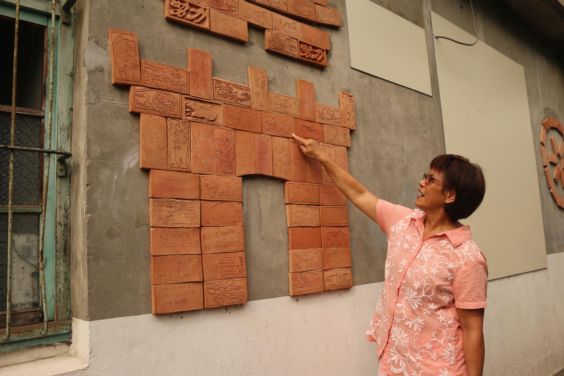 社區發展協會前理事長賴素珍女士講解,社區磚雕裝置藝術的背後故事。攝影/劉建佑