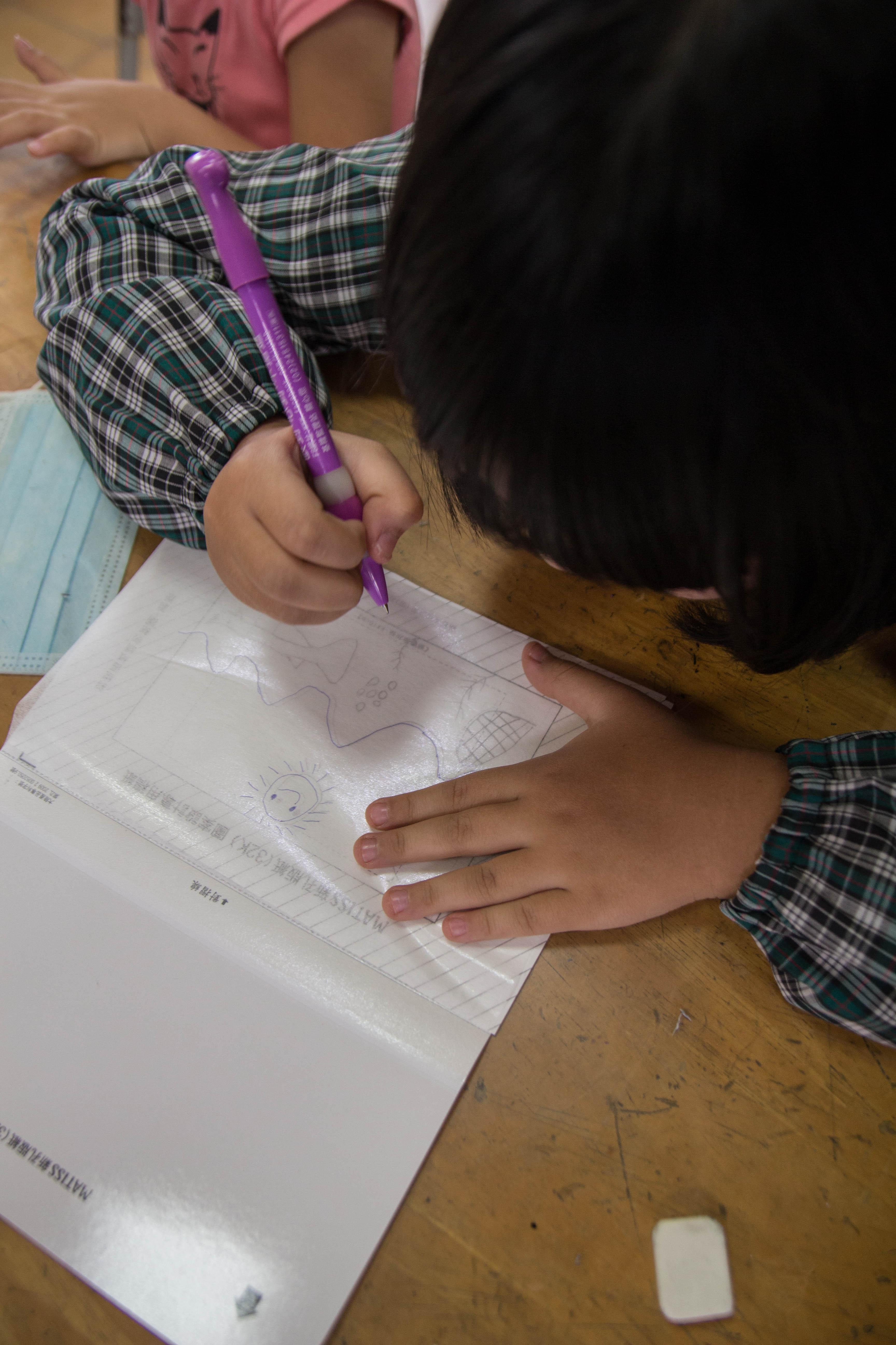小朋友認真的為青鱂魚書籤構圖。 攝影 高子涵