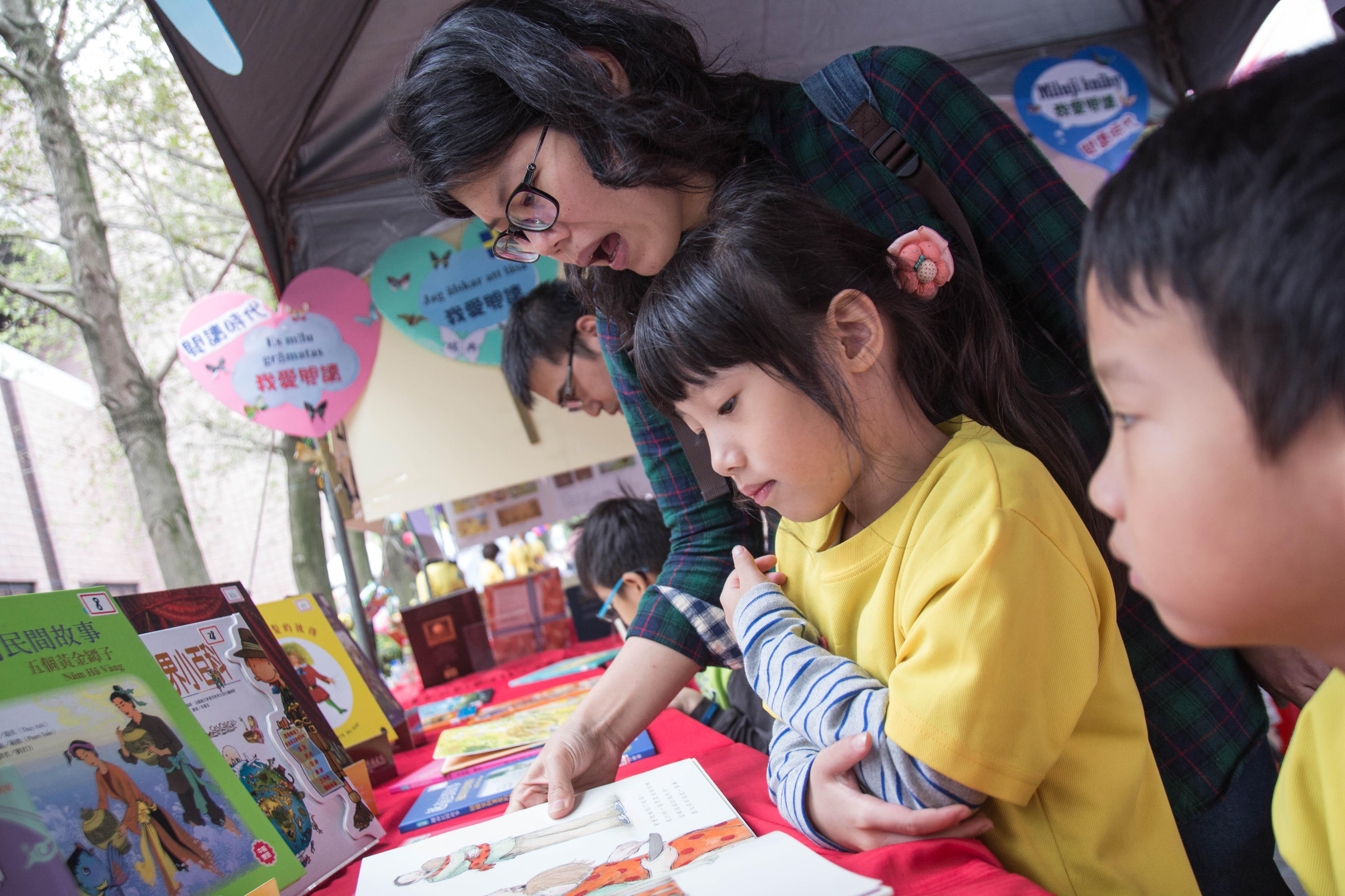 家長陪同孩子參觀攤位,閱讀書籍 攝影/高子涵