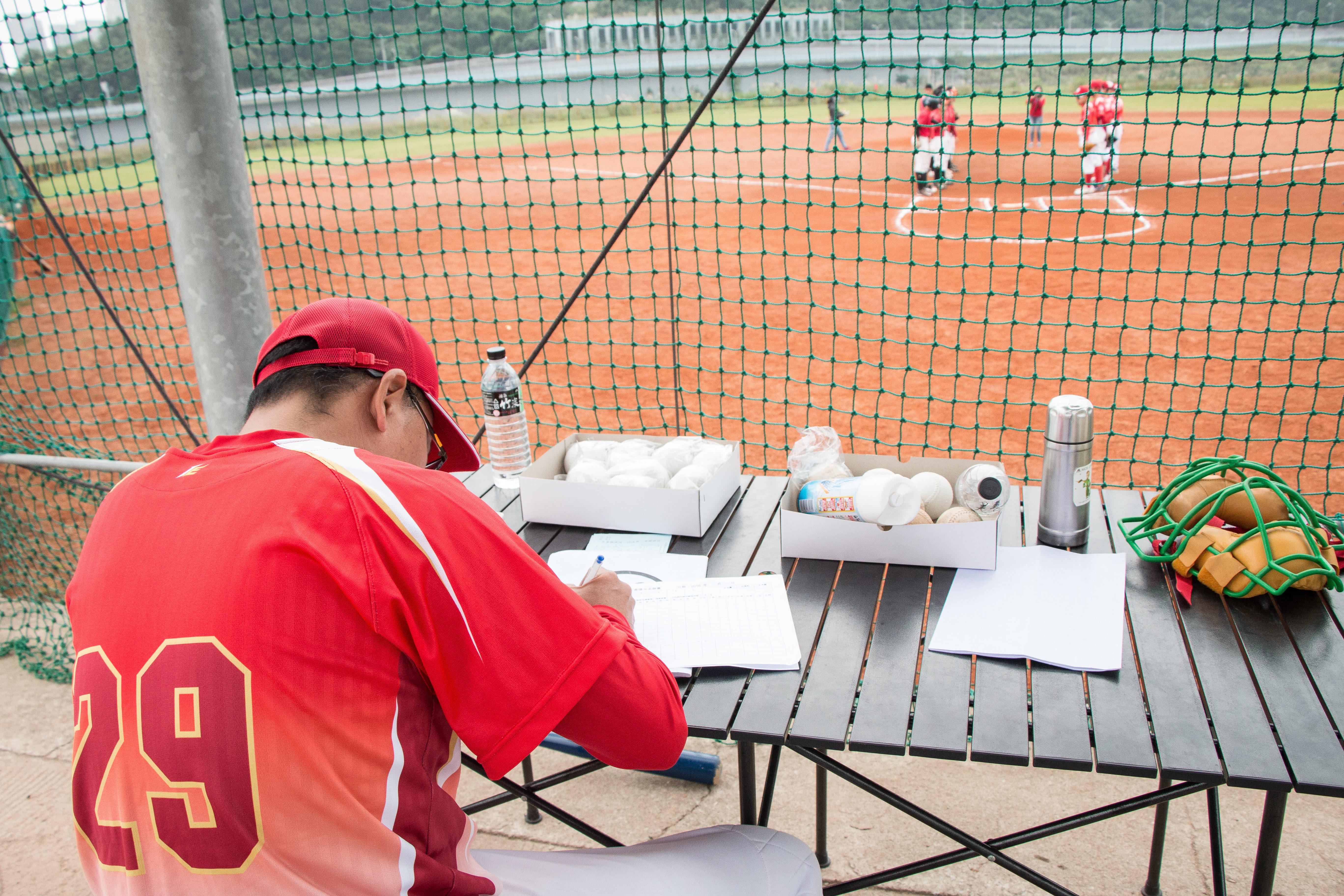 棒球隊人手不足,教練還得充當球員成績紀錄員。攝影/李振均