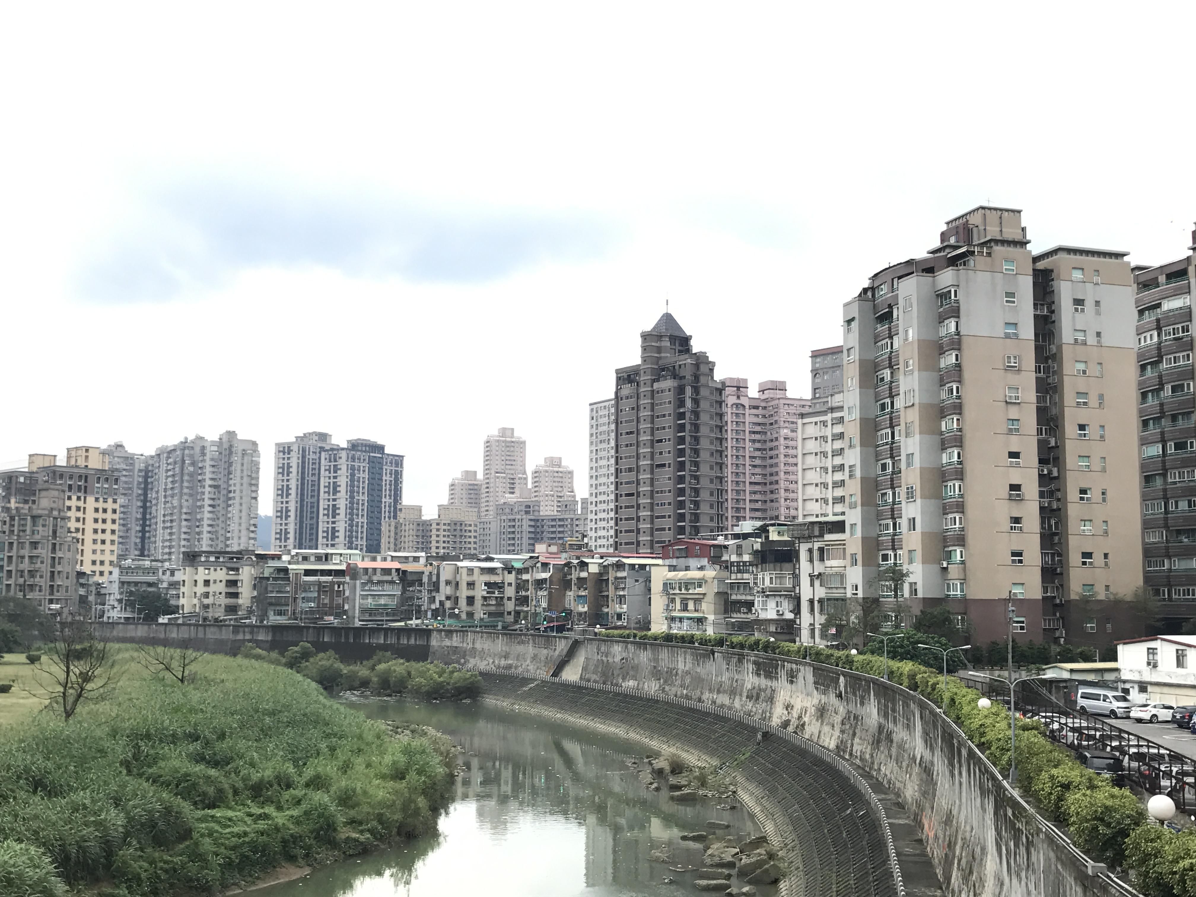 景美溪橋對岸的新北市新店區高樓林立,相較台北市而言,文山區大多屬於低矮的老舊建築,形成強烈對比。攝影/羅紹齊