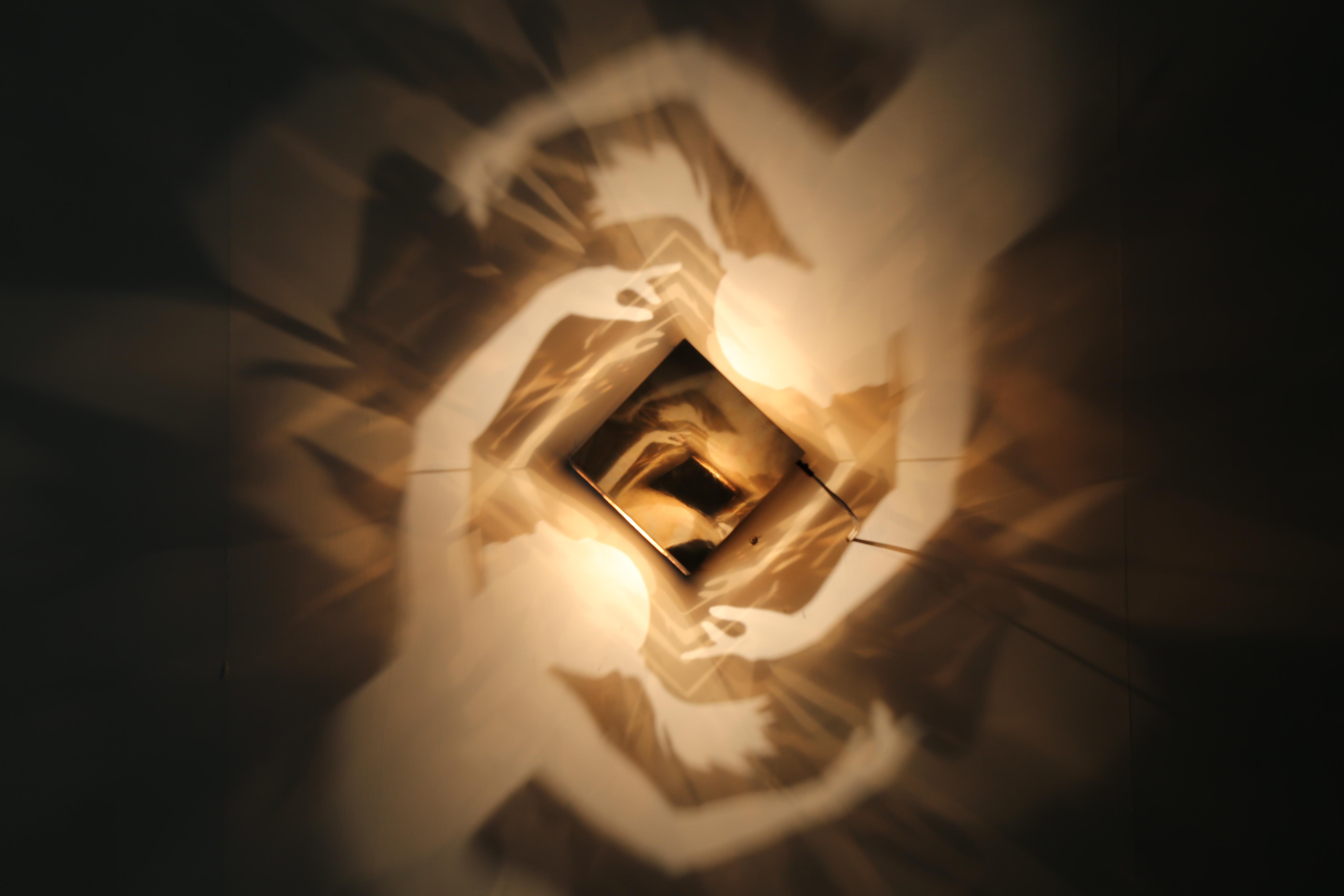 手牽手的人影,象徵著人與人之間的互動。作品以間單的方盒至於中央,再以內部光源照射,傳達出當代生活的多重面貌。 圖/劉佳雯