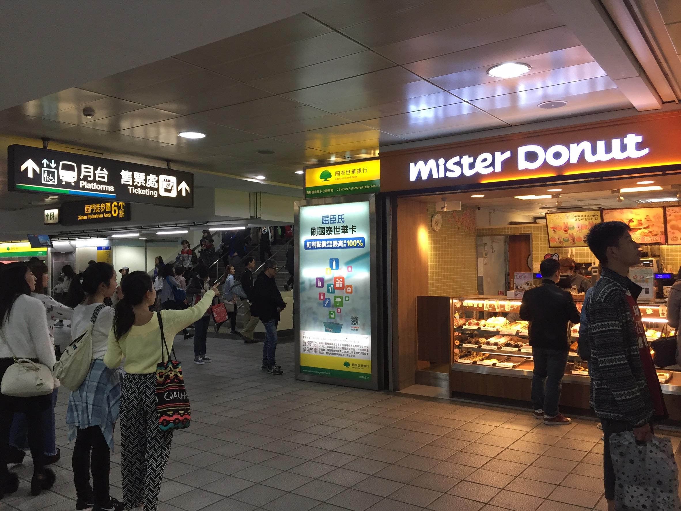 部分捷運站出口可見甜甜圈店面,吸引公共運輸人流。(攝影/謝孟儒)