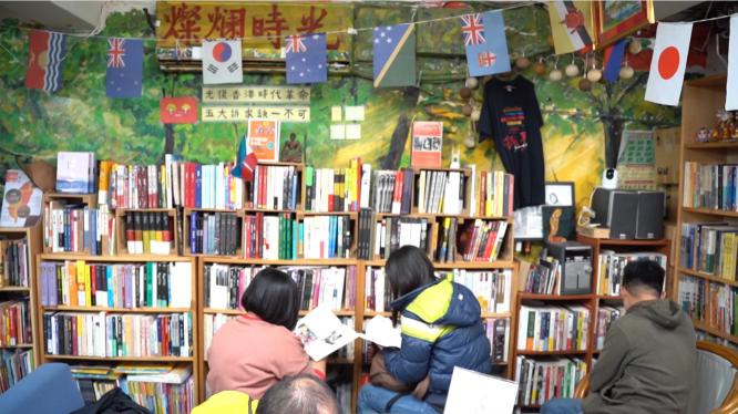 書店內的顧客正在書架前分享選書。攝影/彭 宬